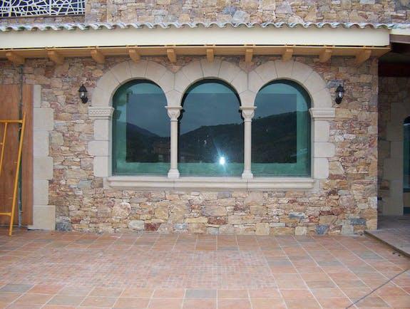 Ventana románica triple con columnas y capiteles